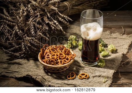 Glass beer with wheat and hops, basket of pretzels on linen cloth on wooden table