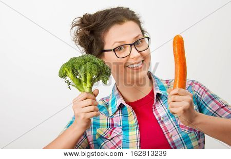 Laughing girl with glasses and broccoli and carrot in the hands in a white background