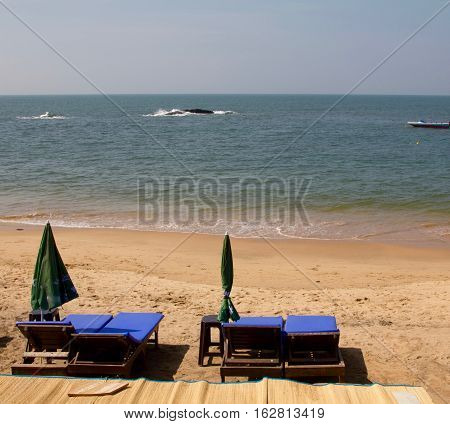 Pairs of blue sunbeds outside a restaurant on a sunny day at the Anjuna beach in Goa, India