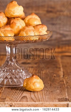 Sweet cream puffs on glass tray on wooden table.