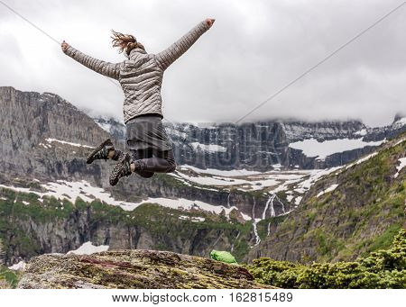 Woman in Warm Clothes Jumps in Excitement overlooking Montana mountains