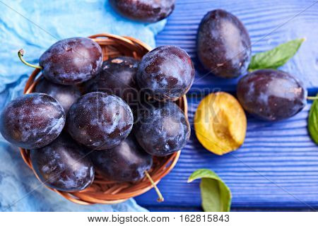 Fresh juicy raw plums in a wicker basket at a blue wooden background. Top view. Concept photo. Universe in one plum