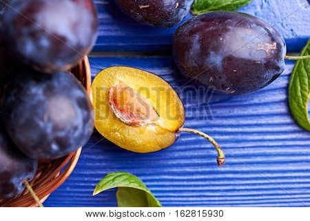 Fresh juicy raw plums in a wicker basket at a blue wooden background. Shallow depth of field. Close view at cutted plum