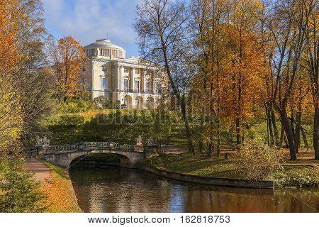 Centaurs bridge over Slavyanka River and Pavlovsk Palace in Pavlovsk park, garden and park reserve in neighborhood of Saint Petersburg, Russia