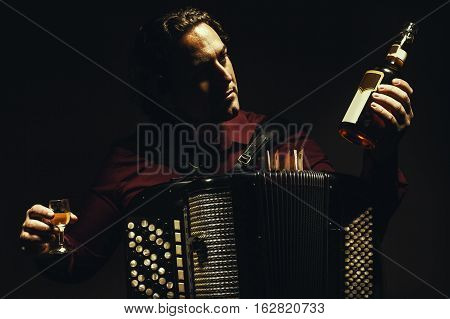 The Chromatic Accordion Player With A Spirit Drink.