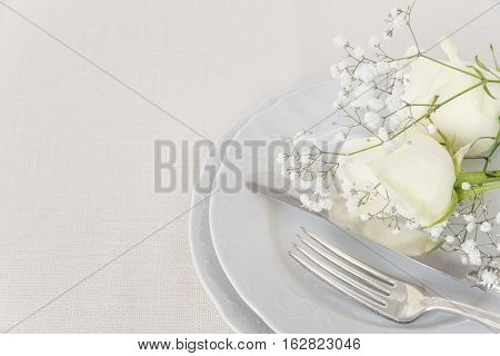 Beautiful decorated table with empty white plates cutlery and white rose flowers on tablecloths with space for text