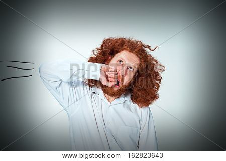 The young angry man with long red hair beating himself