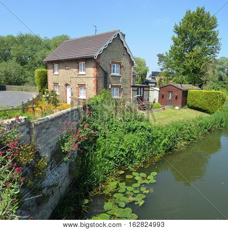OFFORD CLUNY, CAMBRIDGESHIRE, ENGLAND - JUNE 09, 2016: English cottage with colourful cottage garden and wall on the banks of the river Ouse..