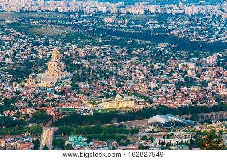 Tbilisi, Georgia. Evening Aerial Panoramic View Of Sameba Complex, Holy Trinity Cathedral Surrounded By Populous Residential Area In Summer Dusk.