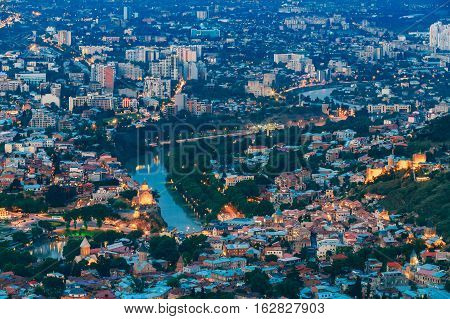 Tbilisi Georgia. Aerial Cityscape With Famous Landmarks: Metekhi Church And Bridge Over Kura River, Narikala Ancient Fortress In Evening Illumination. Populous Residential Area Around In Summer Dusk.