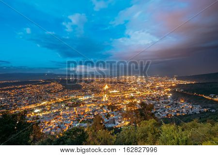 Tbilisi, Georgia. Picturesque Panoramic Aerial Cityscape In Bright Yellow Evening Illumination Under Dramatic Blue And Magenta Sky In Summer Twilight.