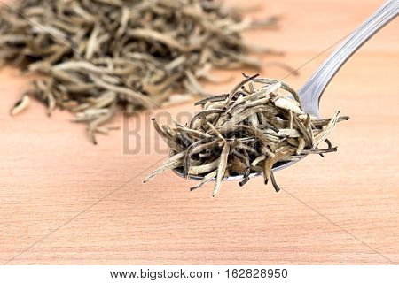 Organic white needle tea on wooden cutting board background