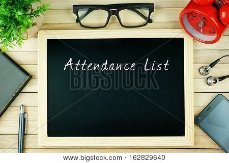 Top view of pen, diary, plant, eye glasses, alarm clock, smartphone, earphone and chalkboard written with ATTENDANCE LIST on wooden background. Business Concept.