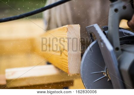 Circular saw cutting through a plank of wood