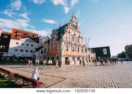 Riga, Latvia - July 1, 2016: Side View Of The Facade Of The Schwabe House At City Hall Square, Ancient Landmark And Popular Touristic Showplace With Walking People Everywhere In Summer Sunny Day Under Blue Sky