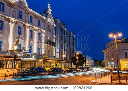 Vilnius, Lithuania - July 8, 2016: Side View Of Facade Of Radisson Blu Royal Astorija Hotel On Illuminated Didzioji Street With Motion Blur Effect In Old Town Under Summer Evening Blue Sky