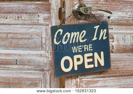 Come In We're Open on the wooden door retro style.