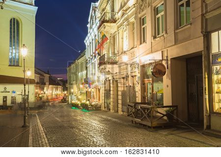 Vilnius, Lithuania - July 8, 2016: View Of Deserted Pilies Street Of Old Town In Bright Evening Illumination, Popular Showplace With Ancient Architecture Under Summer Night Blue Sky.