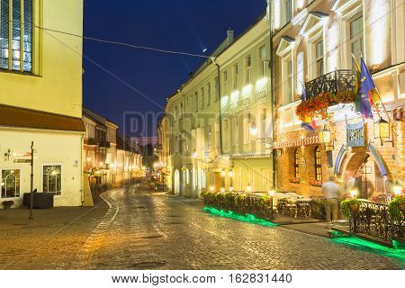 Vilnius, Lithuania - July 8, 2016: The Scenic Deserted Curved Pilies Street Of Old Town In Bright Evening Illumination With Ancient Building And Narutis Hotel Under Summer Blue Sky.