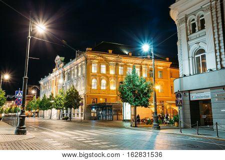 Vilnius, Lithuania - July 8, 2016: The Facades Of Ancient Buildings In Bright Evening Illumination On Deserted Gediminas Avenue, The Main City Street, Famous Landmark Under Dark Black Sky.