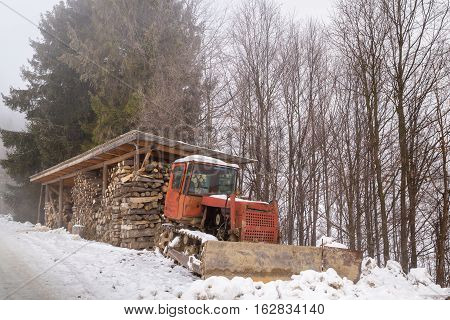Firewood harvested for the winter and a bulldozer near the road in the forest.