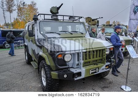 Nizhniy Tagil, Russia - September 25. 2013: Visitors examine military equipment on exhibition range. Scorpion-2M light armored vehicle with grenade launcher for Special Forces. Russia Arms Expo-2013