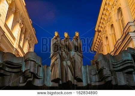 Vilnius, Lithuania. Close The Black Sculpture Of Three Muses On Facade Of Lithuanian National Drama Theatre Building, Main Entrance, Blue Evening Sky Background.