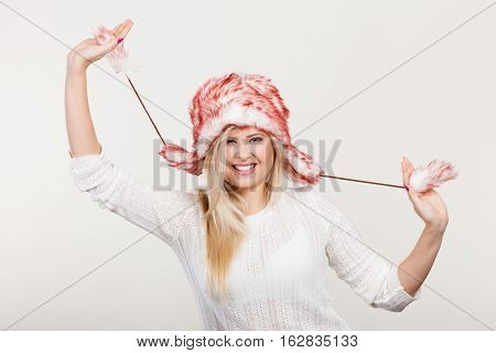 Clothing accessories seasonal clothes concept. Playful happy woman wearing winter furry warm hat having fun