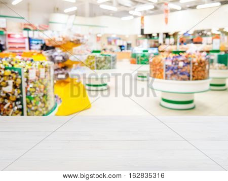 Wooden board empty table in front of of supermarket shelves. Perspective white wood over blur in supermarket. Mock up for display or montage products