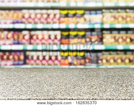 Marble board empty table in front of of supermarket shelves with with hair-dye products. Mock up for display or montage products