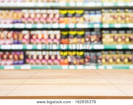 Wooden board empty table in front of of supermarket shelves with with hair-dye products. Mock up for display or montage products