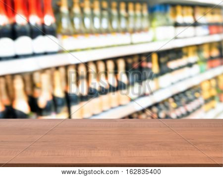 Wooden board empty table in front of of supermarket shelves. Perspective dark wood over blurred alcohol bottlesin supermarket. Mock up for display or montage products