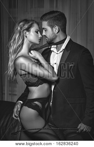 Sexy rich man holded by tie young blonde lover at night black and white