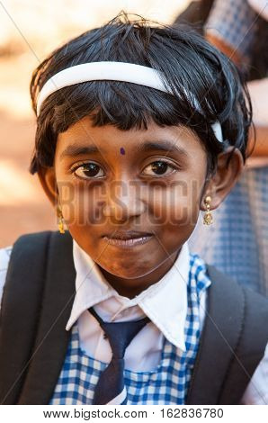 KERALA, INDIA. 23 January 2011: Rural residents in daily life.  Little girl in school uniform. The girl had a traditional Tikka on the forehead and children eye makeup and lips. Chowara, Kerala, South-west India.