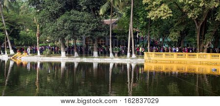 Hanoi, Vietnam - Dec 17, 2016: Vietnamese people matching in line to visit Ho Chi Minh (Uncle Ho) mausoleum and his wooden house, fresh water lake at historic Ba Dinh square.