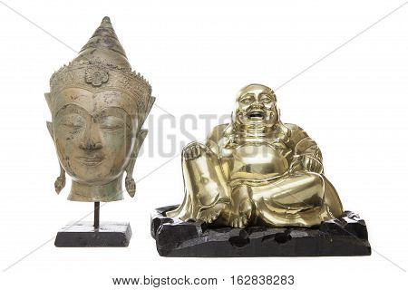 Traditional Buddha head and laughing monk statues. Enlightened Buddha with serene expression in meditation and antique brass laughing monk. Isolated against a white background with cropping options.
