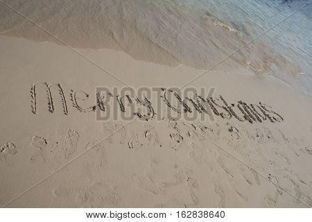 Merry Christmas drew on the sand beach in tropics