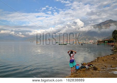 POKHARA, NEPAL: Nepalese woman washing clothes along the shore of Phewa Lake