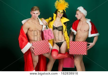 Pretty girl or beautiful woman in golden carnival mask with feathers and sexy lingerie. Handsome muscular men with muscle bodies in red santa suits with Christmas presents on blue wall