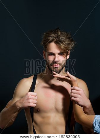 Handsome guy fashion sexy young bearded macho man model with suspenders on pants with female hand on bare muscular torso holds on grey background