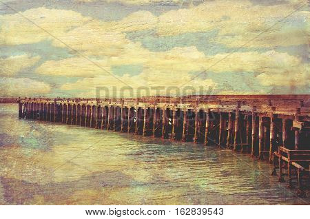 Historic wooden Sumpter Wharf at Oamaru Harbour, New Zealand. Vintage, grunge textured image. Cloud reflections in water. Roosting site for colony of shags (waterbirds).