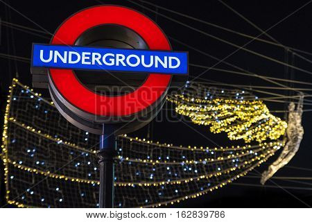 LONDON UK - DECEMBER 20TH 2016: An illuminated sign for an Underground train station in London on 20th December 2016. The London Christmas lights can be seen in the background.