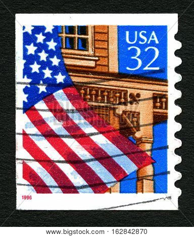 UNITED STATES OF AMERICA - 1ST MARCH 2016: A used postage stamp (circa 1996) depicting an illustration of the American Flag outside a building circa 1996.