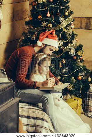 christmas father and daughter in red santa claus hat and sweater writting in book at xmas decorated tree. bearded man with cute girl child at new year holidays celebration
