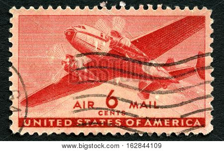 UNITED STATES OF AMERICA - CIRCA 1943: A used US Air Mail postage stamp depicting an illustration of a vintage transport plane circa 1943.