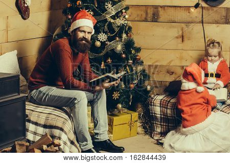 christmas smiling father and children in red santa claus hat and sweater reading book at xmas decorated tree. bearded man with cute kids at new year holidays celebration
