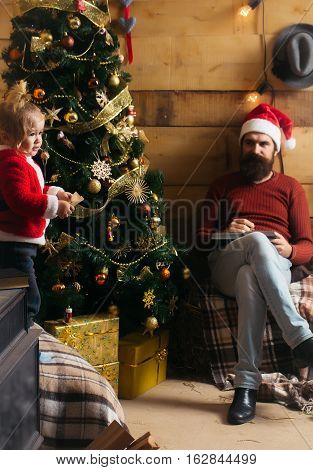christmas father and son in red santa claus hat and sweater reading book at xmas decorated tree. bearded man with cute boy child at new year holidays celebration near plaid