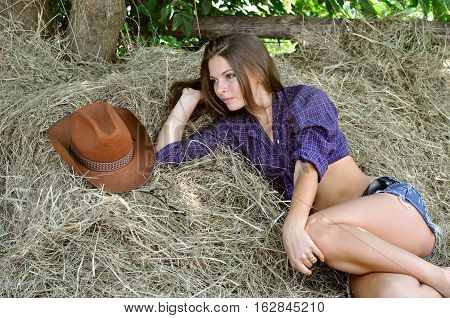 young attractive woman in cowgirl style lying on haystack in summer day