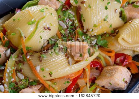 Close Up Of Salmon With Large Pasta And Vegetables In A Black Plate