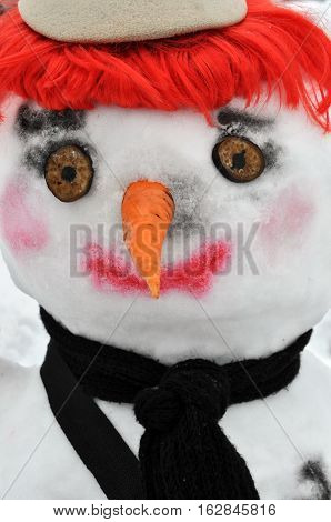 close-up of snow man with red wig black scarf and bonnet